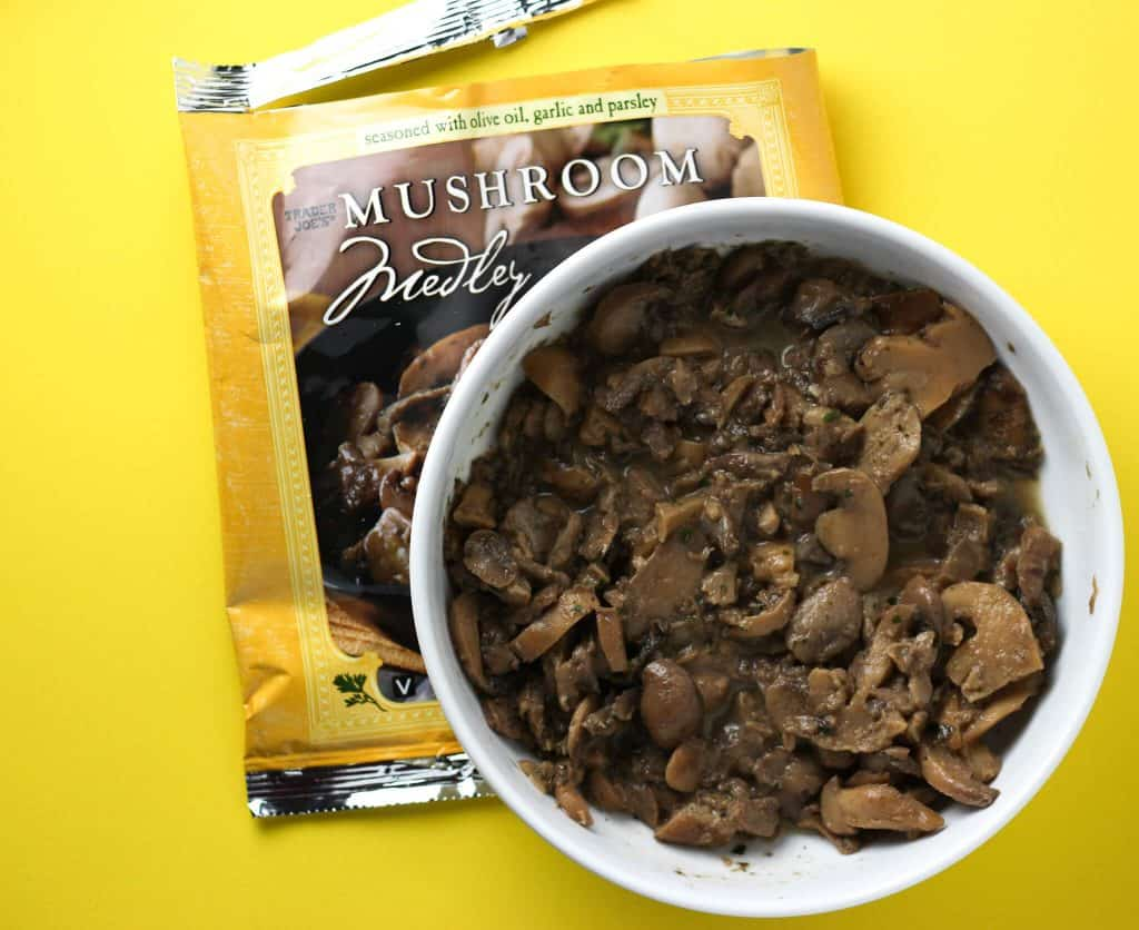 Trader Joe's Mushroom Medley cooked next to the bag on a yellow background
