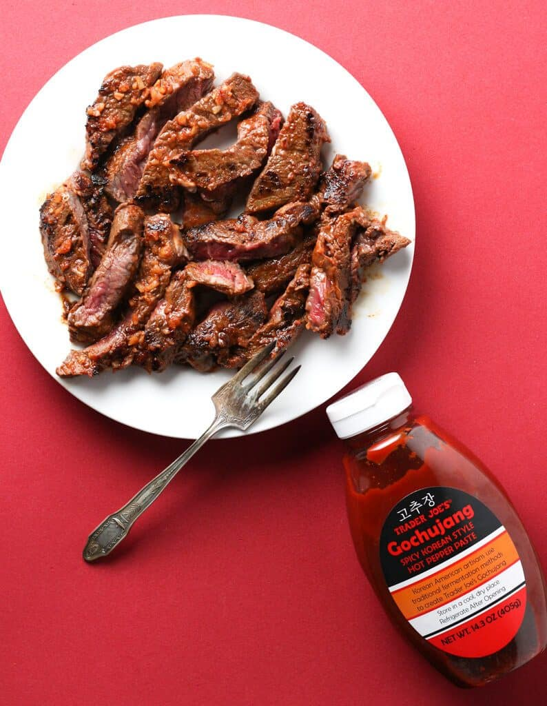 Trader Joe's Gochujang and steak on a white plate with red background
