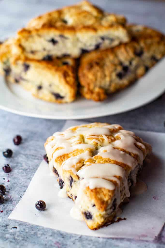 One glazed blueberry scone with a plateful of scones in the background with blueberries scattered throughout