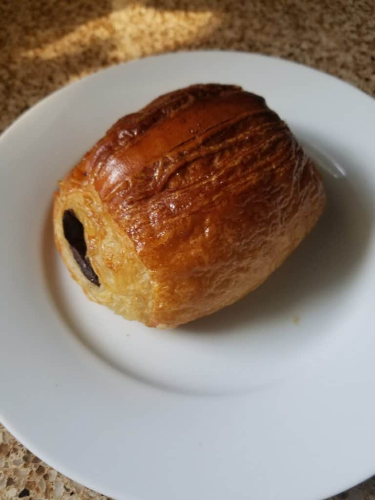 Trader Joe's Chocolate Croissant fully baked and on a white plate.