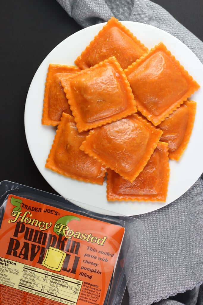 A plate full of fully cooked Trader Joe's Honey Roasted Pumpkin Ravioli with a grey napkin on a black background