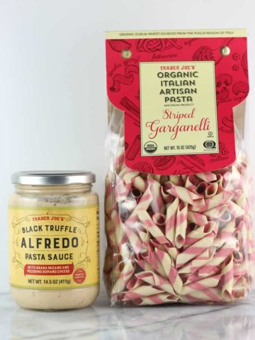 An unopened jar of Trader Joe's Black Truffle Alfredo Pasta Sauce and a bag of unopened Organic Italian Garganelli