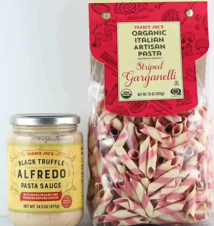 An unopened jar of Trader Joe's Black Truffle Alfredo Pasta Sauce and a bag of unopened Organic Italian Garganelli
