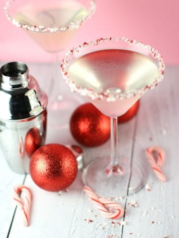 Two Holly Jolly Peppermint Martinis next to a cocktail shaker, red ornaments, and a scattering of candy canes