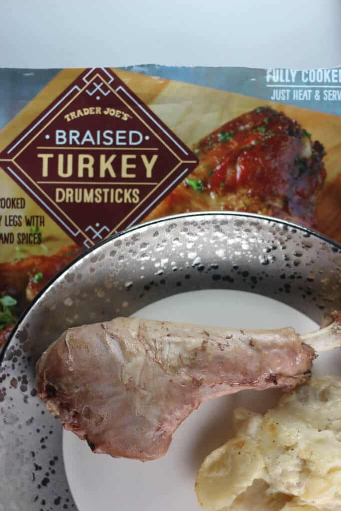 A fully heated through Trader Joe's Braised Turkey Drumsticks on a plate with scalloped potatoes