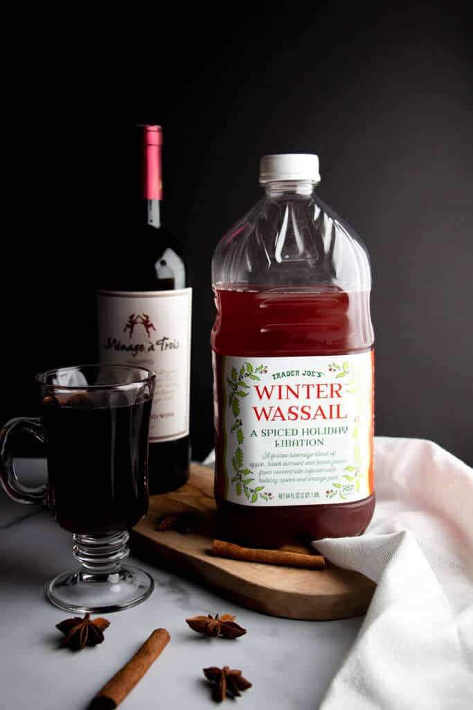 A bottle of Trader Joe's Winter Wassail next to wine, spices and a finished mulled win