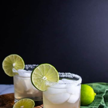 Two finished Spicy Jalapeno Limeade Margarita garnished with limes