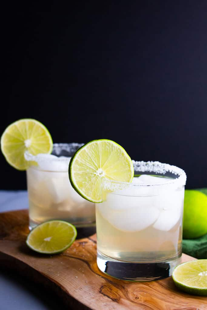 A closer look at two finished spicy jalapeno limede margaritas that have been garnished with lime wheels