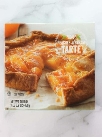 An unopened box of Trader Joe's Peaches and Cream Tarte on a marble surface