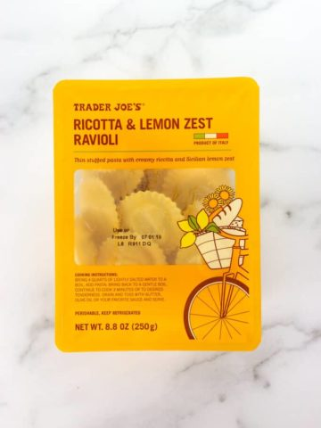 An unopened box of Trader Joe's Ricotta and Lemon Zest Ravioli on a marble surface