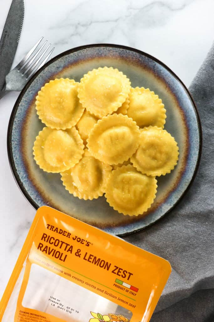 Trader Joe's Ricotta and Lemon Zest Ravioli fully cooked on a plate with a napkin and the original packaging