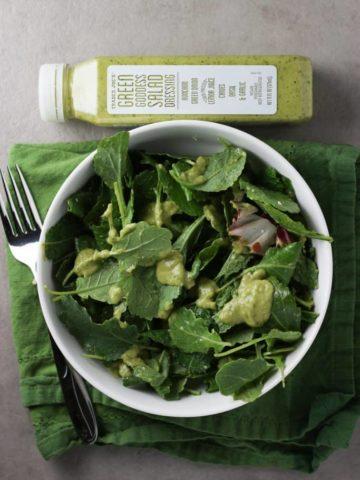 Trader Joe's Green Goddess Salad dressing on a salad next to the jar, a napkin, and fork,