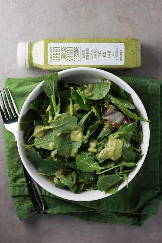 Trader Joe's Green Goddess Salad dressing on a salad next to the jar, a napkin, and fork,