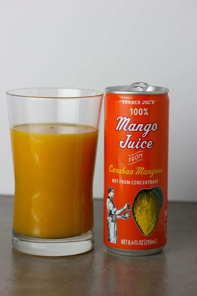 Trader Joe's 100% Mango Juice from Carabao Mangoes poured into a glass to reveal the bright orange color and thickness.