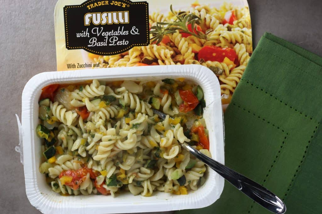 Trader Joe's Fusilli with Vegetables and Basil Pesto mixed together with a fork and green napkin below the dish.