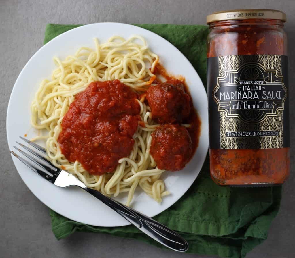 Trader Joe's Italian Marinara Sauce with Barolo Wine jar next to plate of spaghetti with two meatballs