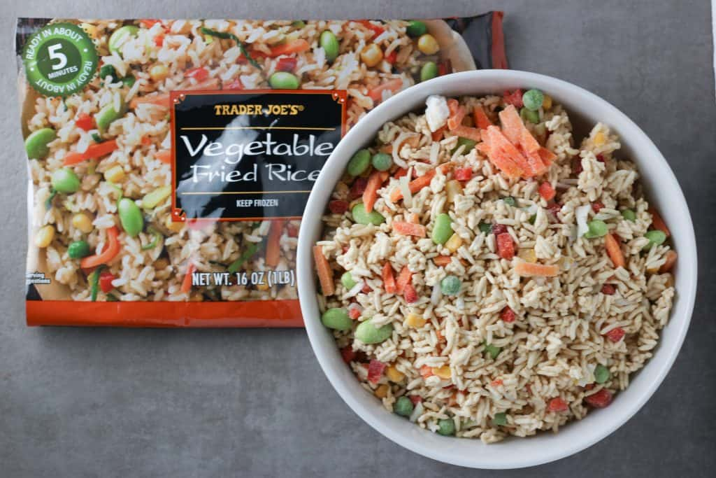 Trader Joe's Vegetable Fried Rice still frozen and not cooked next to the original bag.