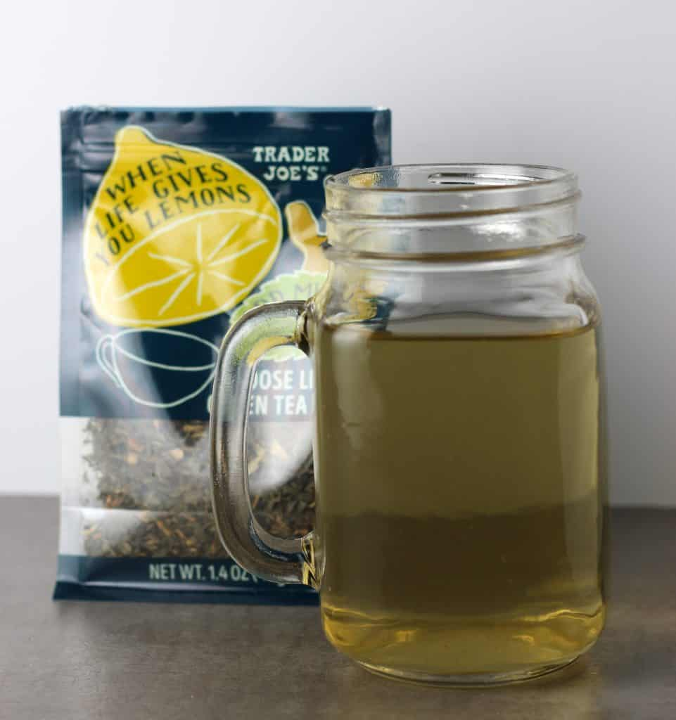 Trader Joe's When Life Gives You Lemons Loose Leaf Green Tea Blend brewed next to the bag in a clear cup