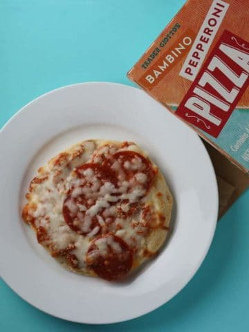 Trader Joe's Bambino Pepperoni Pizza baked pizza next to the box.