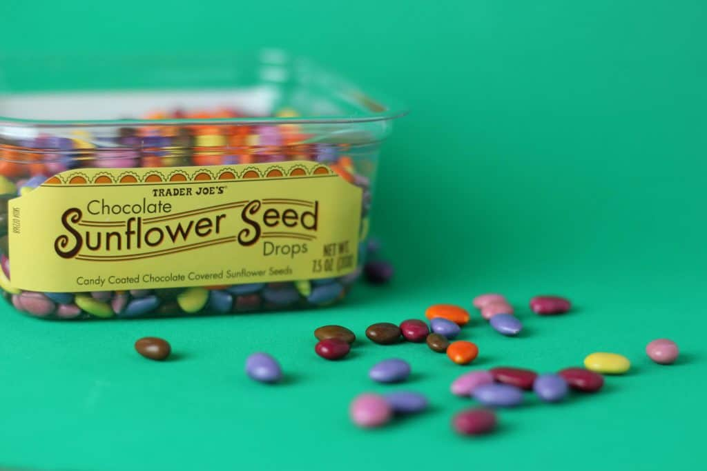 Trader Joe's Chocolate Sunflower Seed Drops with some drops displayed in front of the plastic container