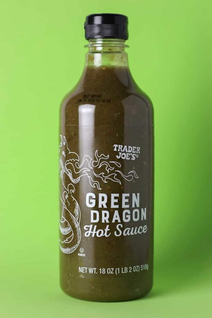 Trader Joe's Green Dragon Hot Sauce bottle on a green surface