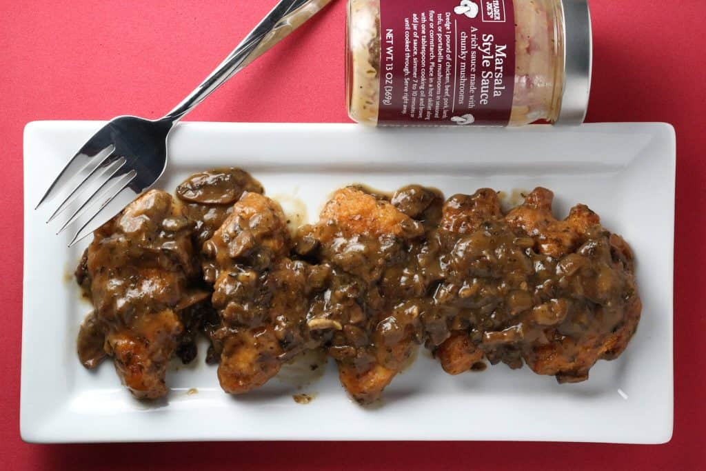 Trader Joe's Marsala Style Sauce on top of chicken on a white rectangular plate