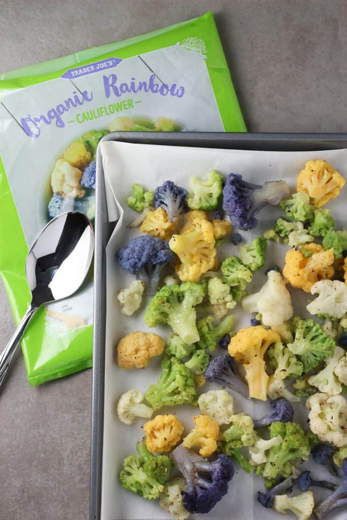 Trader Joe's Organic Rainbow Cauliflower roasted and on a sheet pan next to the bag.