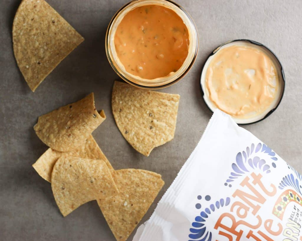 Trader Joe's Restaurant Style White Corn Tortilla Chips next to Trader Joe's Queso Dip