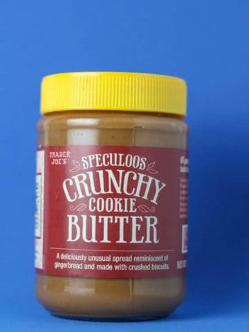 Trader Joe's Speculoos Crunchy Cookie Butter in a jar with a blue background.