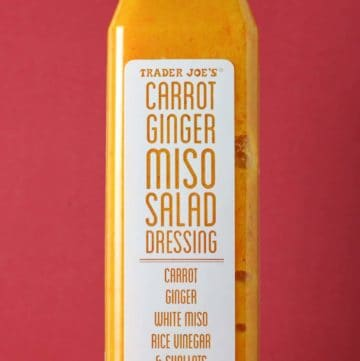 Trader Joe's Carrot Ginger Miso Salad Dressing bottle on a red background