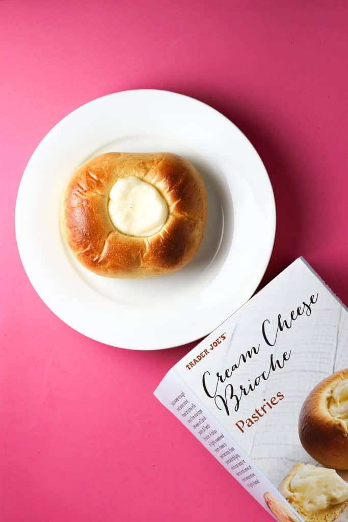Trader Joe's Cream Cheese Brioche Pastries baked on a white plate next to the box