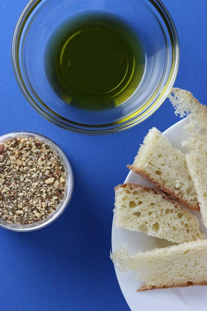 Trader Joe's Dukkah with some bread and olive oil on a blue background.