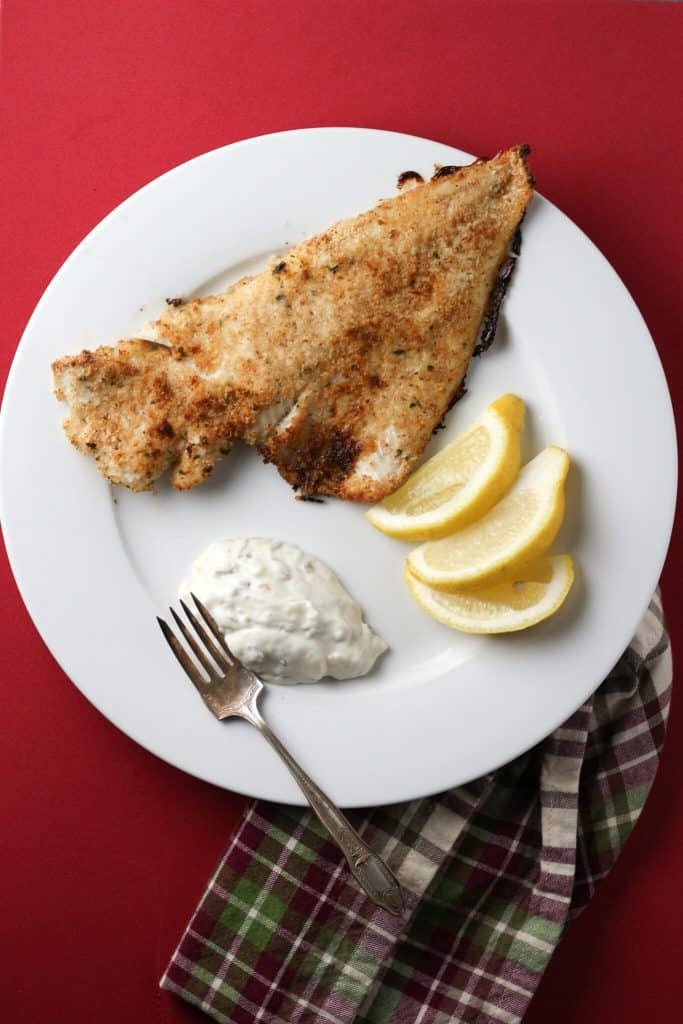 Trader Joe's Wild Fresh Haddock oven fried served on a white plate with lemon and tartar sauce