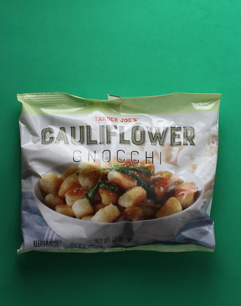 An unopened bag of Trader Joe's Cauliflower Gnocchi bag on a green background