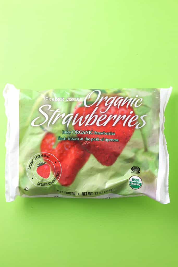 Trader Joe's Frozen Organic Strawberries bag on a green background