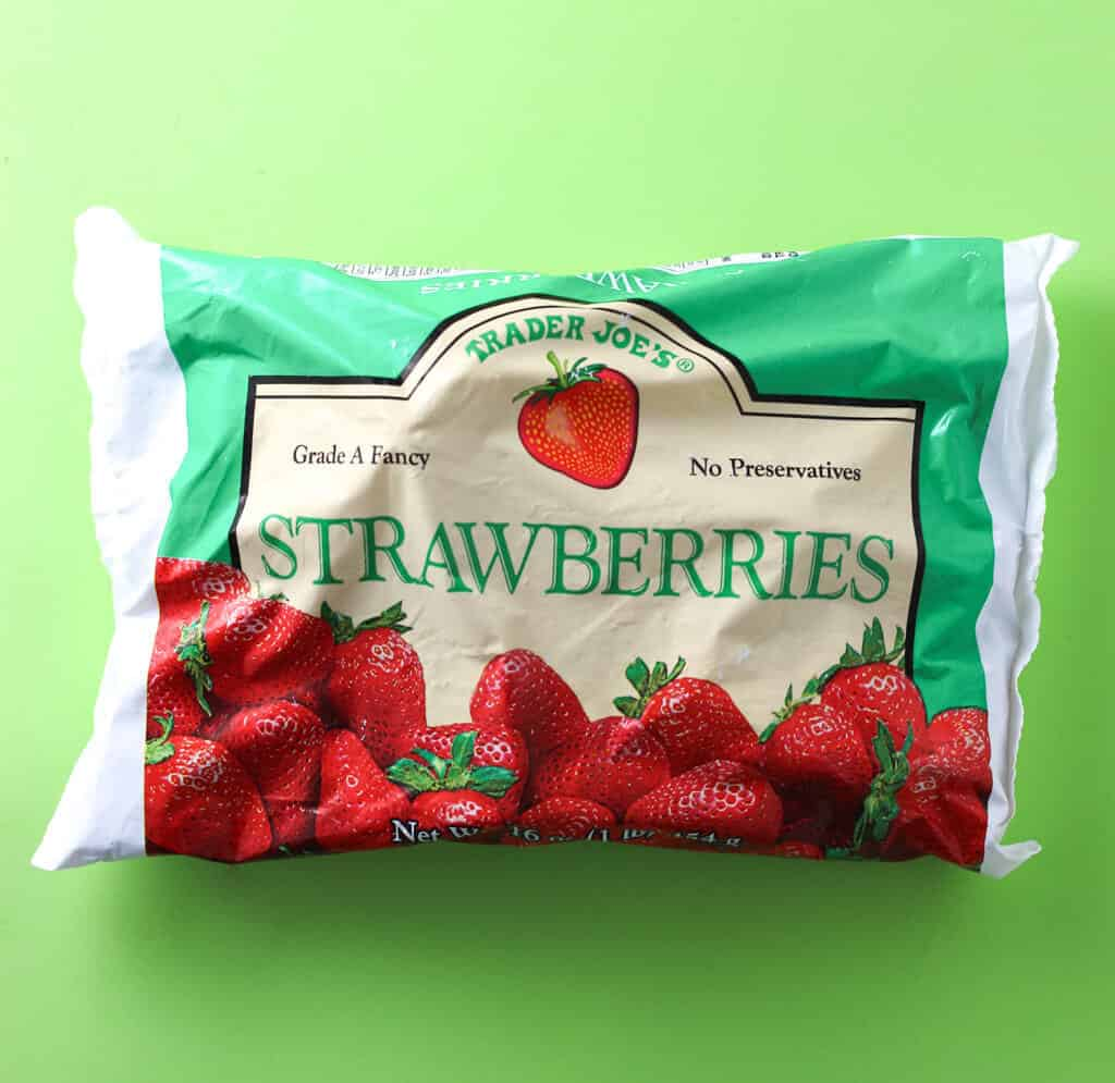 Trader Joe's Frozen Strawberries bag on a green background