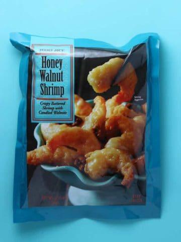 An unopened package of Trader Joe's Honey Walnut Shrimp bag on a blue background