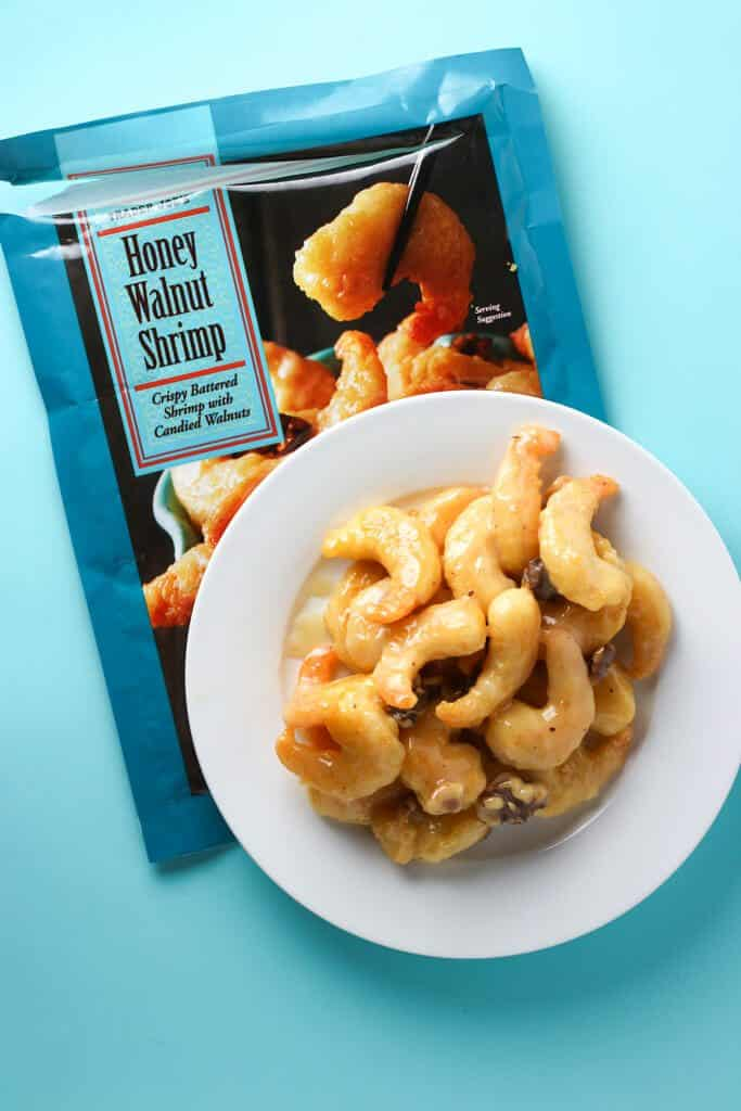Trader Joe's Honey Walnut Shrimp prepared on a white plate with blue background
