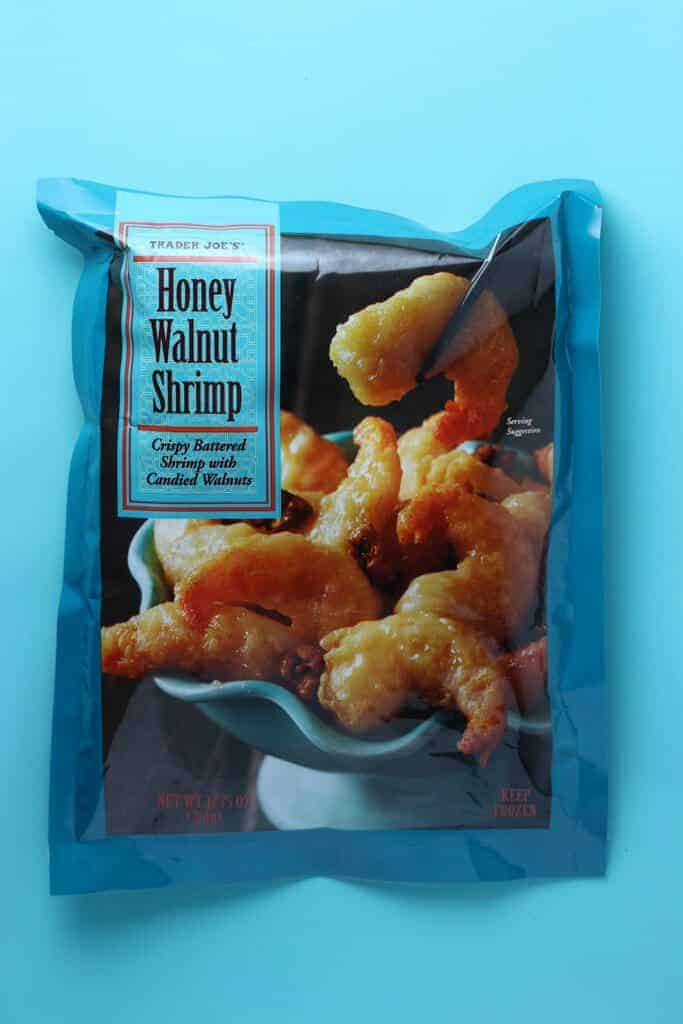 An unopened package of Trader Joe's Honey Walnut Shrimp bag on a blue background