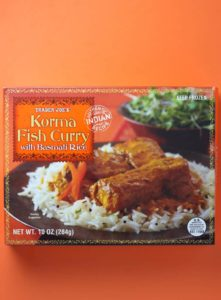An unopened box of Trader Joe's Korma Fish Curry box as sold in stores on an orange background