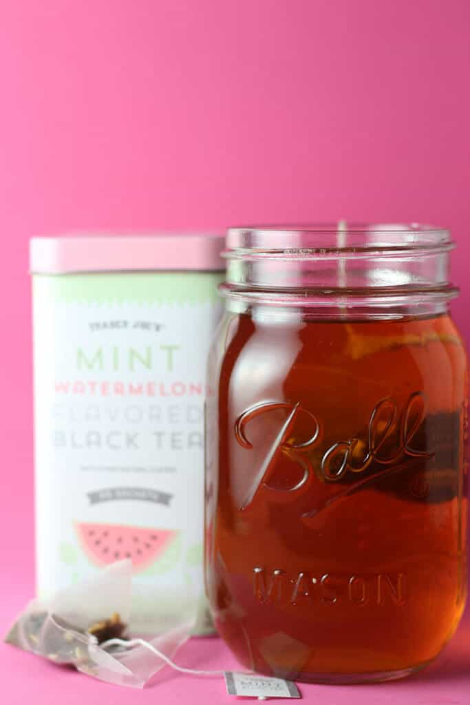 Trader Joe's Mint Watermelon Flavored Black Tea brewed in a mason jar on a pink background