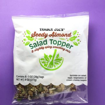 Trader Joe's Seedy Almond Salad Topper bag on a purple background