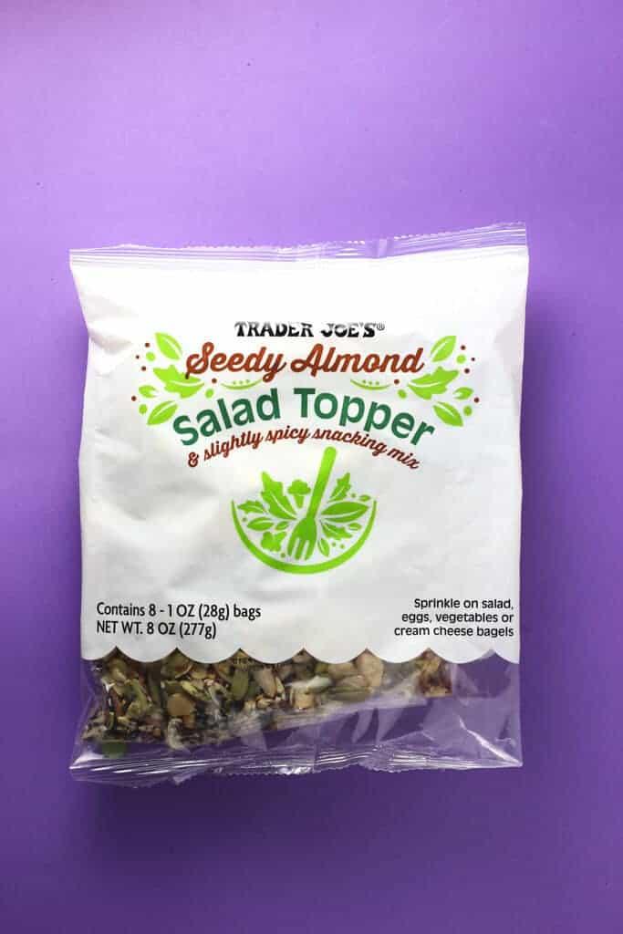 Trader Joe's Seedy Almond Salad Topper bag on a purple background