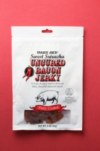 Trader Joe's Sweet Sriracha Uncured Bacon Jerky bag on a red background