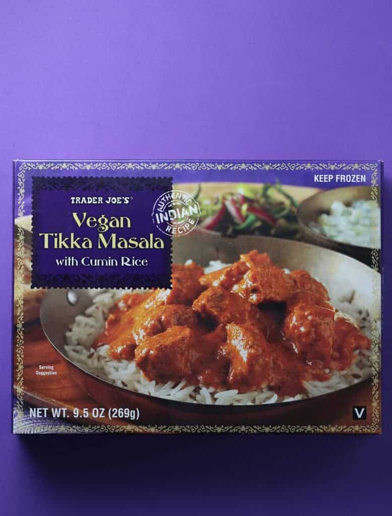 An unopened box of Trader Joe's Vegan Tikka Masala box on a purple background