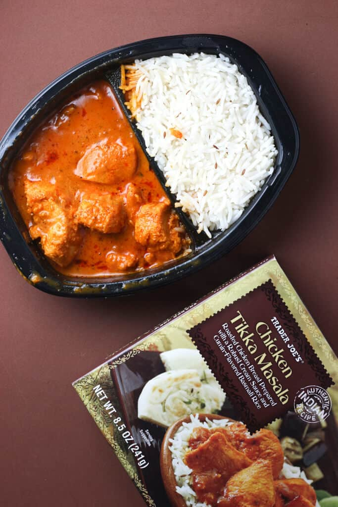 Trader Joe's Chicken Tikka Masala out of the microwave, on a brown background next to the box it came out of.