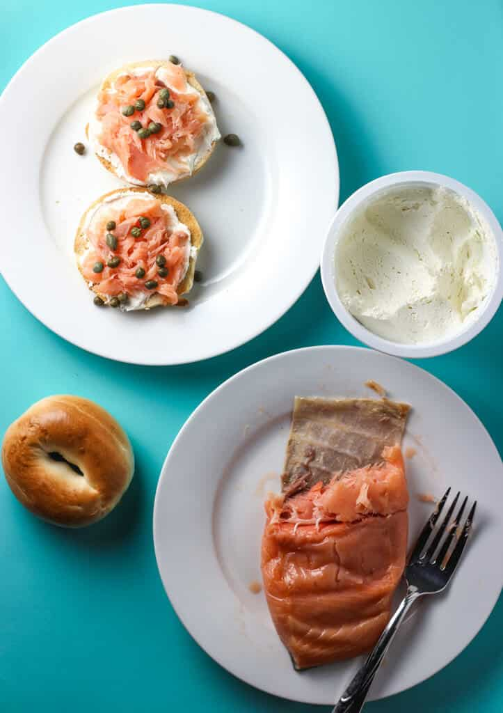 Trader Joe's Hot Smoked Scottish Salmon served with bagels, cream cheese on a blue background.
