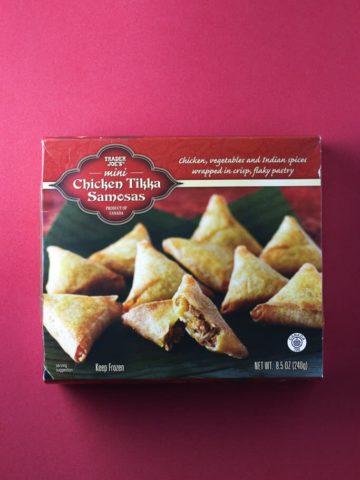Trader Joe's Mini Chicken Tikka Samosas box on a red background