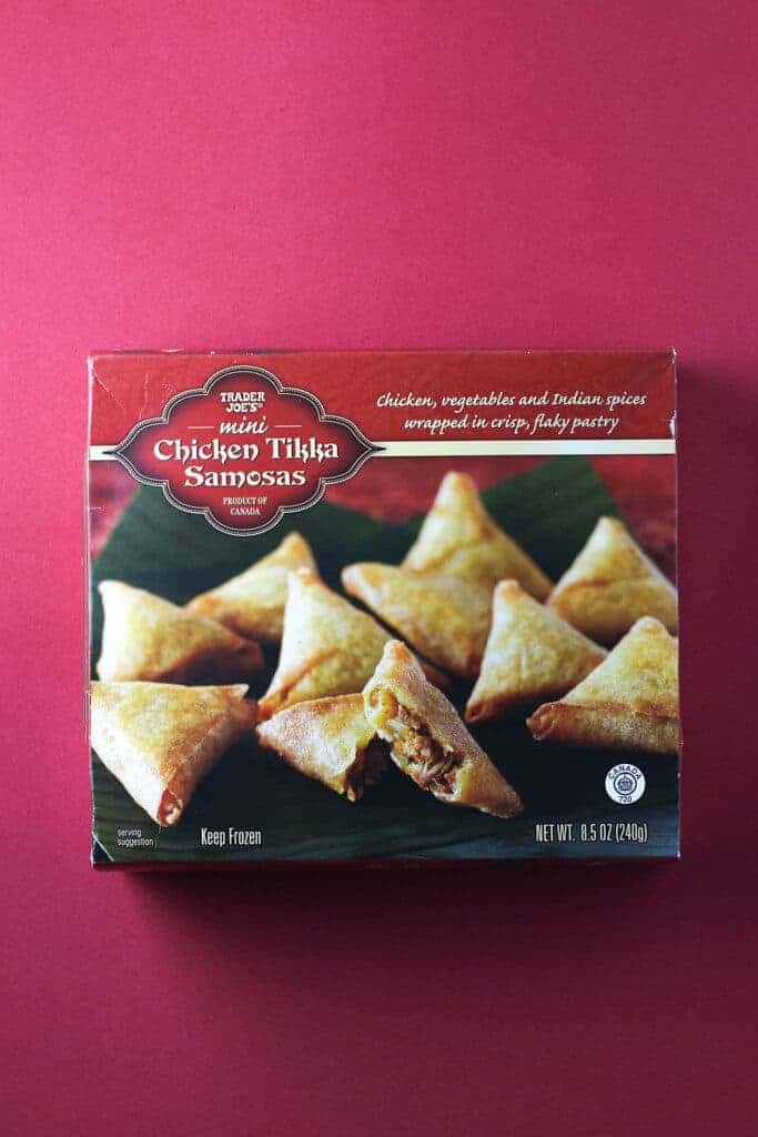 Trader Joe's Mini Chicken Tikka Samosas box on a red background