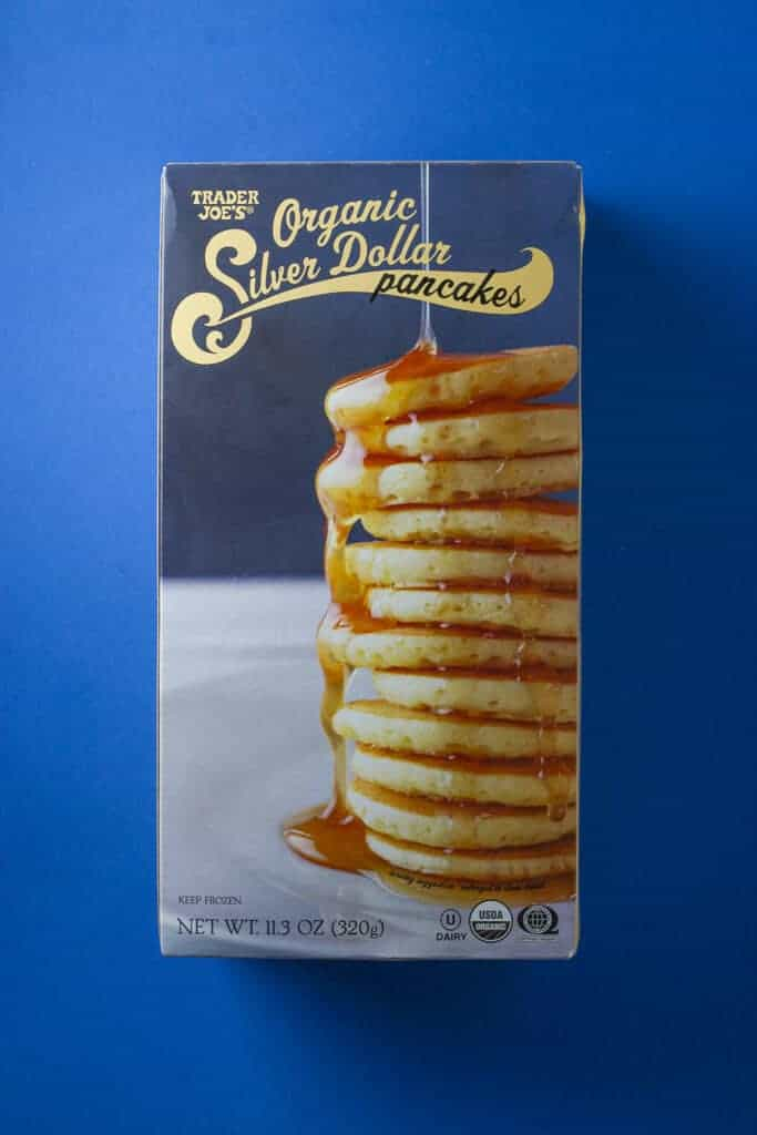 An unopened box of Trader Joe's Organic Silver Dollar Pancakes box on a blue background